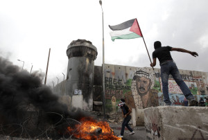 Palestinians hold a flag and throw a stone during clashes with Israeli troops at Qalandiya checkpoint