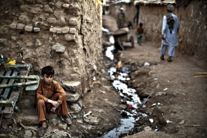 An Afghan refugee youth, sits on the side of the alley of a poor